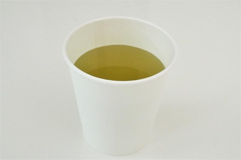 コップにいれたサントリー天然水 澄みわたるお茶
